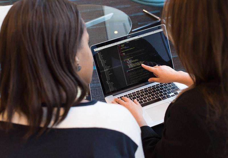 women at computer desk code